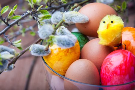 Coloured eggs, base and yellow chicken toy-  the symbol of Easter Stock Photo