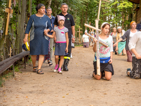 orison: Grabarka, Poland - August 14, 2016: Pilgrims of the Orthodox Church moving on knees around the church  on the Holy Mount of Grabarka. Editorial