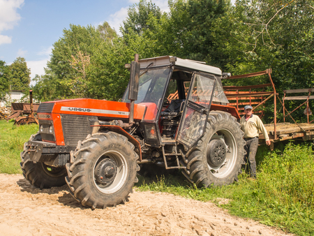 agronomist: Wolka Zamkowa, Poland - August 13, 2016: Farmer by his  big red tractor
