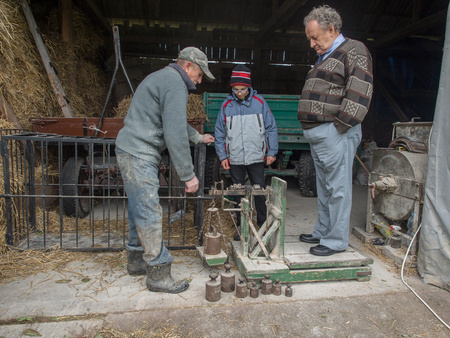 rustiness: Bobrek, Poland - November 13, 2016:  An  old man measuring weight using  an  old weighing scale Stock Photo