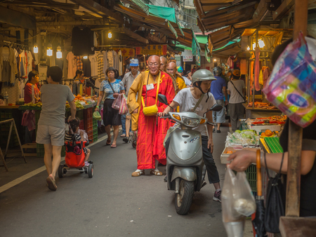 fare: New Taipei City,Taiwan - October 04, 2016: Buddhist monks praying and collecting  donations on  a local market Editorial