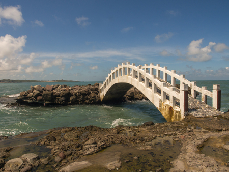 Shimen, Taiwan - October 03, 2016: A white bridge between the rocks on the shore of the ocean in Shimen Art, northern Taiwan Editorial