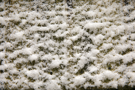 erratic: Background, texture. Uneven white coating of snow on a dark surface.