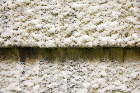 Background, texture. Uneven white coating of snow on a dark surface.