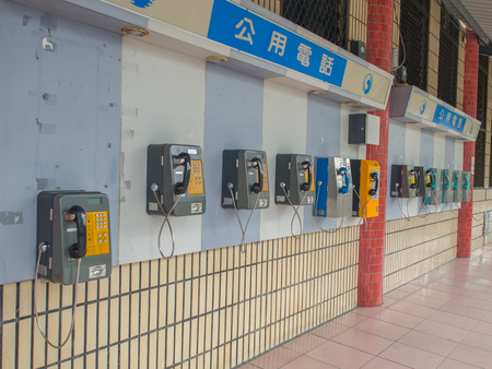 knell: Luodong, Taiwan - October 18, 2016: More than a dozen of phones installed on the wall of a railway station building in Luodong Editorial