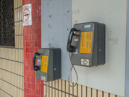 Luodong, Taiwan - October 18, 2016: More than a dozen of phones installed on the wall of a railway station building in Luodong Stock Photo - 81026190