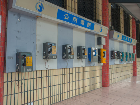 Luodong, Taiwan - October 18, 2016: More than a dozen of phones installed on the wall of a railway station building in Luodong Stock Photo - 81026191