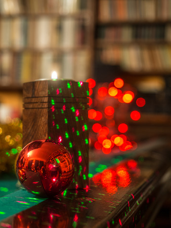 Christmas candle and bauble over  the dark background with red bokeh, pool table and bookcase of plenty of books.