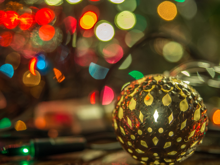 Christmas bauble over dark background with colorful, blurred  lights (bokeh) Stock Photo