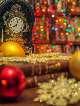 Christmas ornaments, bauble and clock over the background with  bookcase of plenty of books.