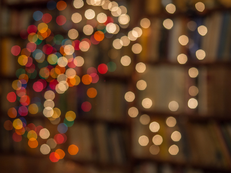 Blurred colorful Christmas lights background over dark background with library. Abstraction.
