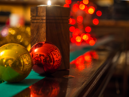 Christmas candle and bauble over  the dark background with red bokeh and pool table