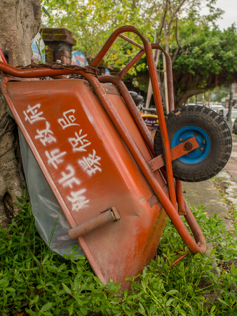 Taipei, Taiwan - October 08, 2016: Red wheelbarrow with Chinese inscriptions leaned on a tree trunk