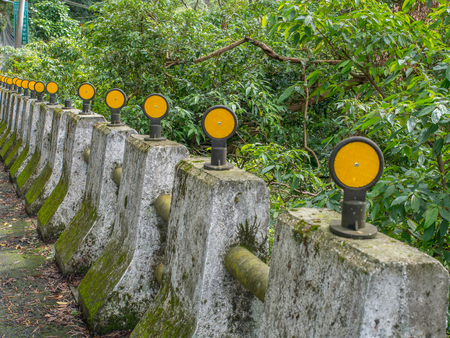 Concrete pillars  bumpers with yellow reflectors along asphalt road