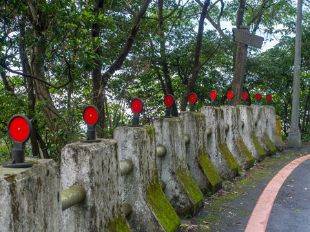 Concrete pillars  bumpers with red reflectors along asphalt road Stock Photo