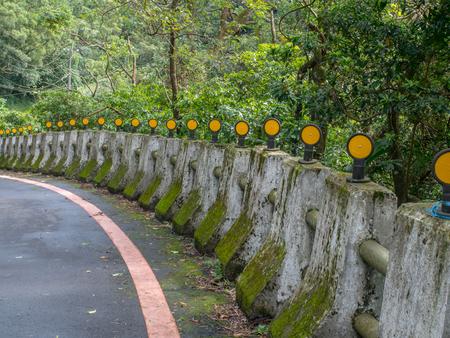 아스팔트 도로를 따라 노란 반사체가있는 콘크리트 기둥  범퍼 스톡 콘텐츠