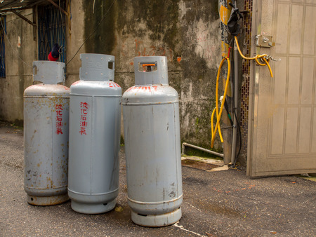 Taipei, Taiwan - October 08, 2016: Gray, metallic gas cylinders with a damaged wall of a brick building in a background Stock Photo