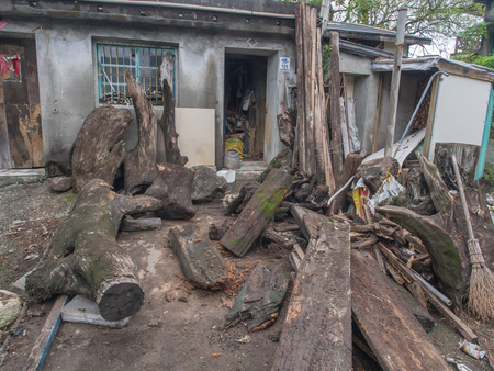 Roots, boards and other decayed tree by Taiwanese brick house