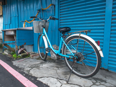 Taipei, Taiwan - October 08, 2016: Blue bicycle and sink  with a blue garage door in a background on the streets of Taipei
