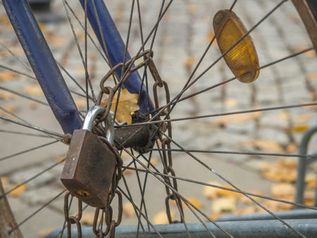 Rusty padlock with a chain attached to a bicycle wheel Stock fotó