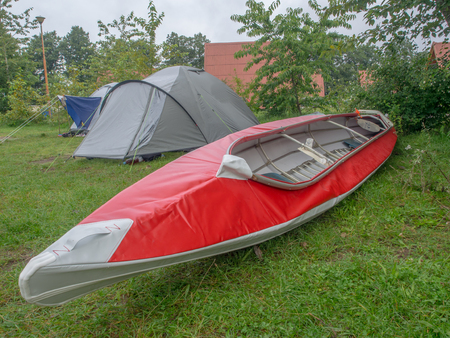 Red folding kayak and the tent on the grass