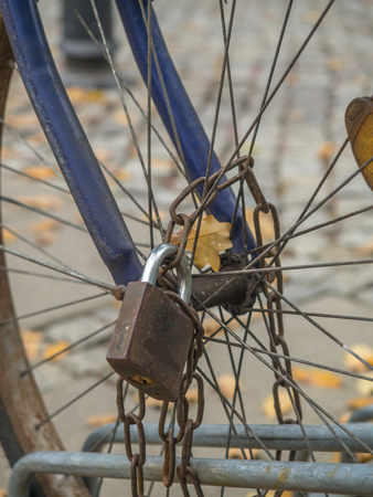 Rusty padlock with a chain attached to a bicycle wheel Stock Photo