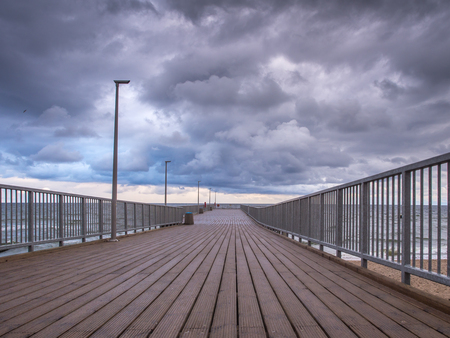 Empty wooden pier in Chlopy fisherman village during cloudy weather