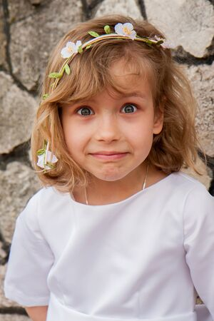 A girl in a white dress with a surprised face and bulging eyes