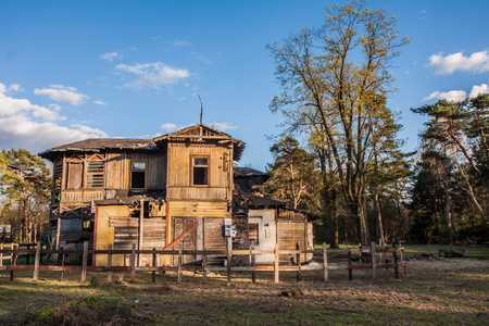 Otwock, Poland: Fenced and destroyed wooden house in sunshine Stock Photo