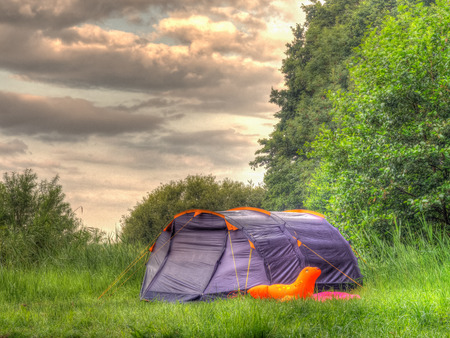 Grey tent in a forest clearing Stock Photo