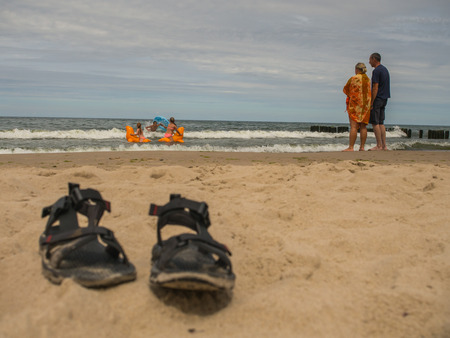Mielno, Poland - July 31, 2016: Parents  pair standing on  a shore and  watching their  children bathing