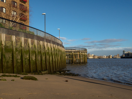 London, England - December 08, 2015: View to the Canary Wharf from the sandy beach of Thames River