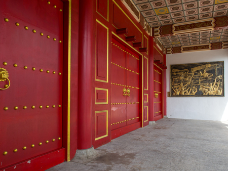 Taipei, Taiwan - October 20, 2016: Blood-red wooden door to  a temple with gold borders