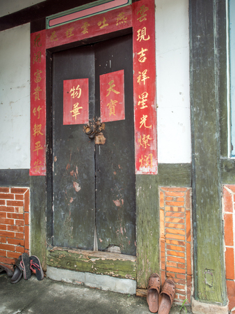 Yilan, Taiwan - October 13, 2016: Wooden, decorative and a little damaged  door to a old residential taiwanese house. . Editorial
