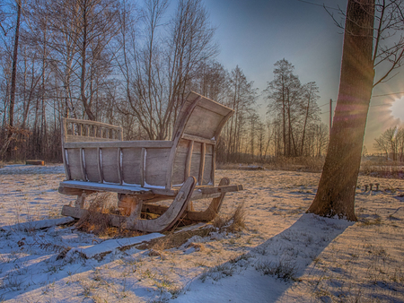 Wooden sleigh in a  snowy field in  rays of a  rising sun