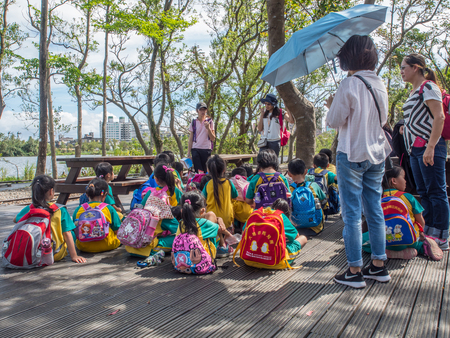 Luodong, Taiwan - October 18, 2016: A group of Taiwanese preschool children with colourful backpacks on a trip to Luodong Forestry Culture Garden