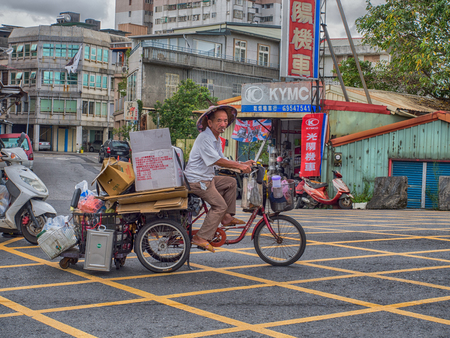Luodong, Taiwan - October 18, 2016: Taiwanese man carrying different items on a three-wheeled bicycle. Tricycles  are  very popular means of transportation for older people in Taiwan