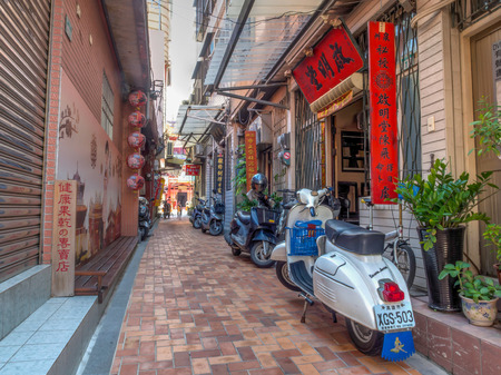 Tainan, Taiwan - October 11, 2016: Four colourful scooters along the small street in Tainan