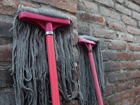 Floor cleaning brushes leaning against a brick wall Stock fotó