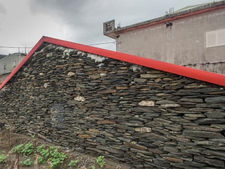 Ilan, Taiwan - October 13, 2016: Wall home built with black, flat stones