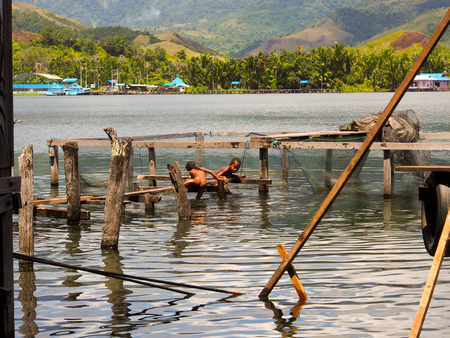 Sentani,  Indonesia - January 24, 2015: Children play happily jumping from a bridge into the water on the shore of Sentani Lake Editorial