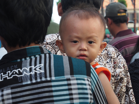 Jakarta, Indonesia - January 11, 2015: Small Indonesian child, with beautiful eyes, carried through the crowded streets by the parent.