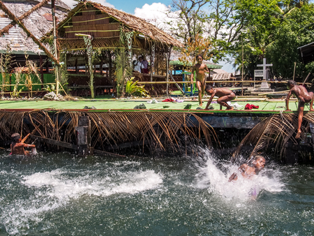 Sentani,  Indonesia - January 24, 2015: Children play in the water on a shore of Lake Sentani