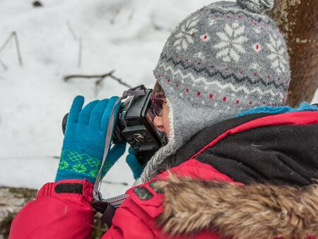 A  woman takes a picture with a reflex camera during winter