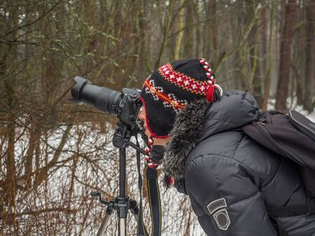 Woman taking a  winter picture holding her camera on a tripod