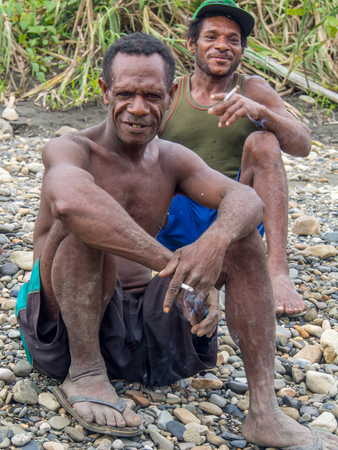 Mabul,  Indonesia - January 12, 2015: Raiders of gold from the village of Mabul sitting on a bank of a river and enjoying  a view of arriving tourists