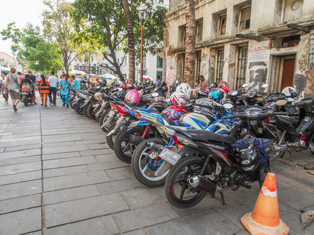 Jakarta,  Indonesia - January 11, 2015: Several rows of motorcycles  with  destroyed, brick building of Jakarta in  a background