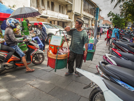 Jakarta,  Indonesia - January 11, 2015: Street seller  carrying his merchandise walks  on a sidewalk  passing set parked in a row motorcycles