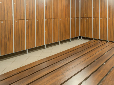 The row of wooden cabinets and a wooden bench in a fitness club dressing room Stock Photo