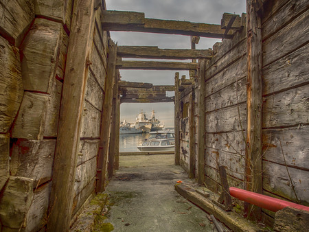 View of the port of Bergen through the walls of burnt wooden house